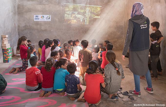 スクリーンで映像を楽しむシリアの子どもたち