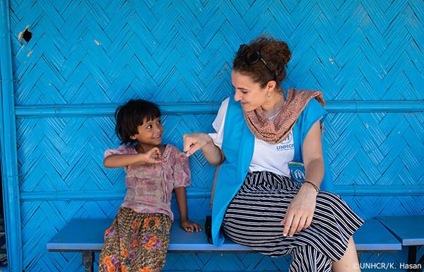 写真:UNHCR職員と話すロヒンギャ難民の少女