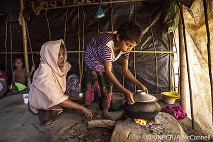 写真:調理器具セットで食事をとるロヒンギャ難民