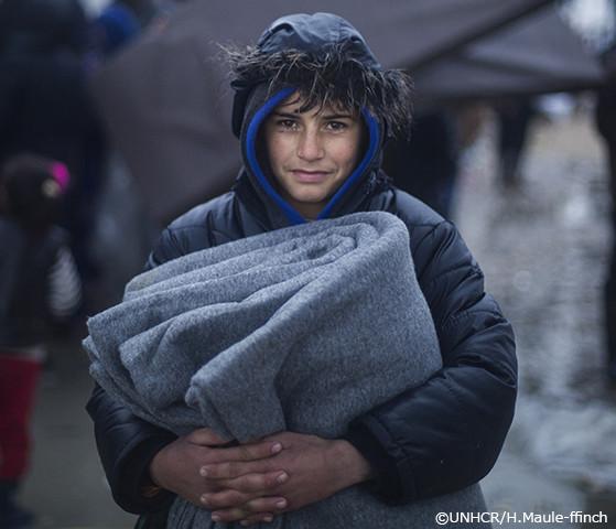防寒支援物資を受け取った難民の少年の写真