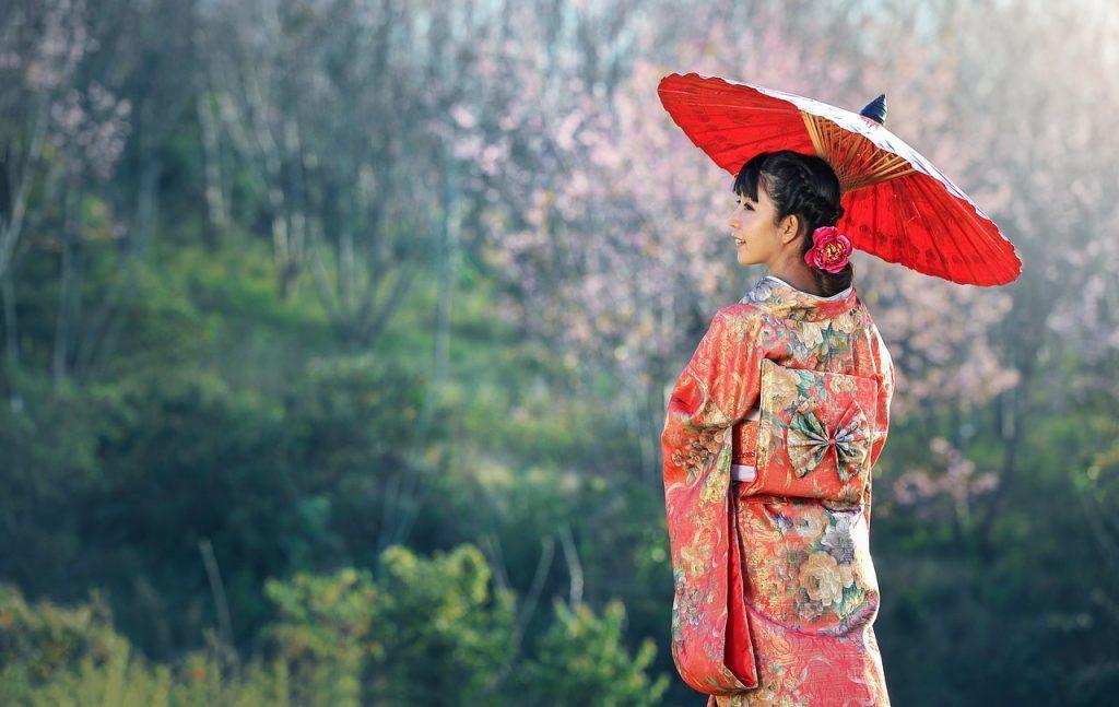 晴れ着姿の女性が番傘を指して立っている