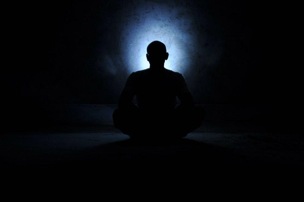 薄明りの中で座禅を組む人の影
