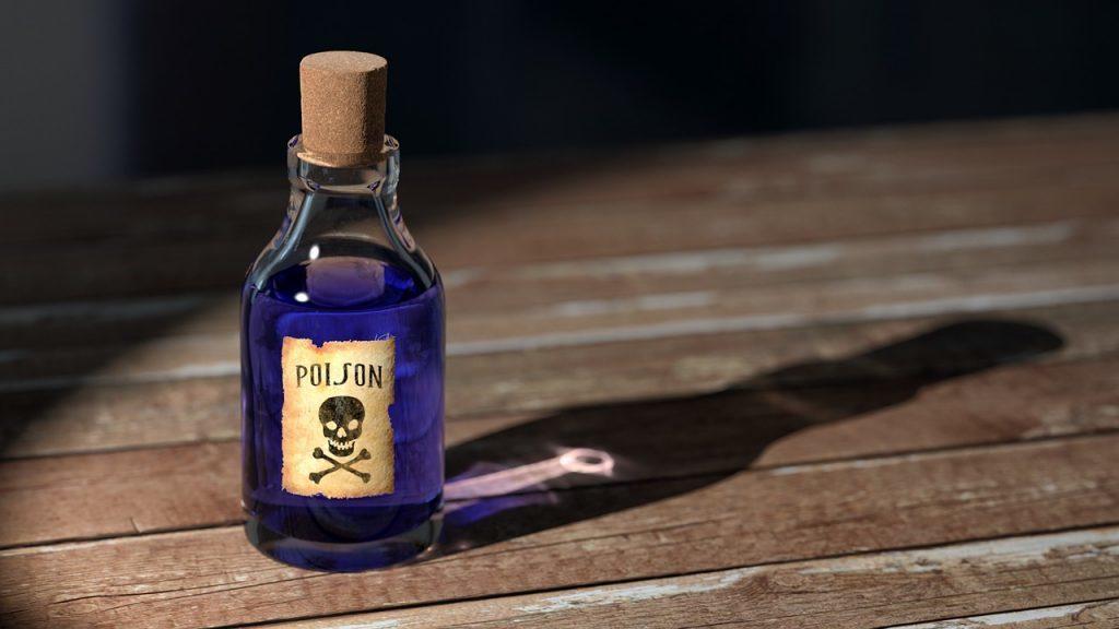 どくろマークの書かれた小瓶が木の机に置かれ、光が当たっている