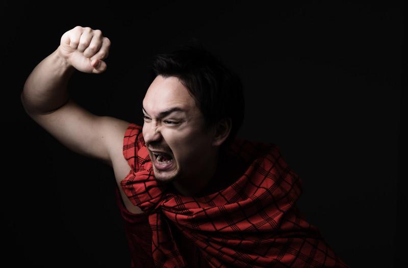 拳を振り上げて怒りをあらわにする赤いトガをまとった男性
