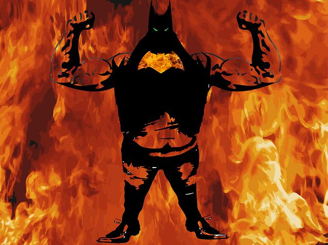 炎を背景に両腕の筋肉を誇示する短足のマスクの男性