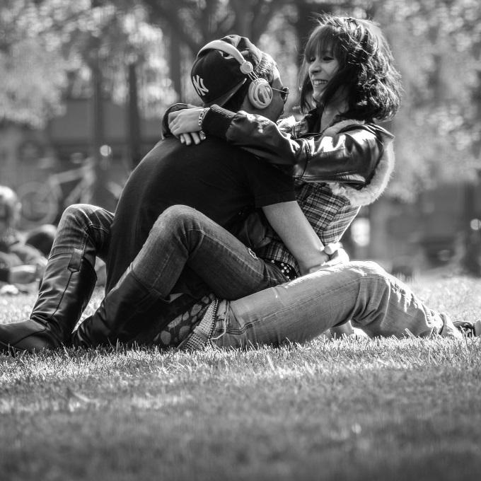 芝生の上で抱き合う男女
