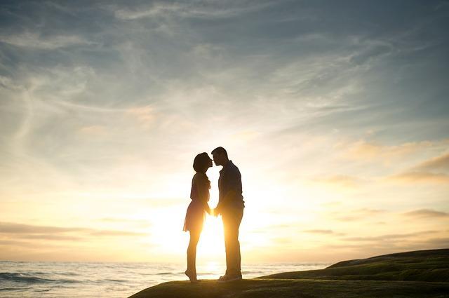 夕日の海辺でキスする瞬間のカップル