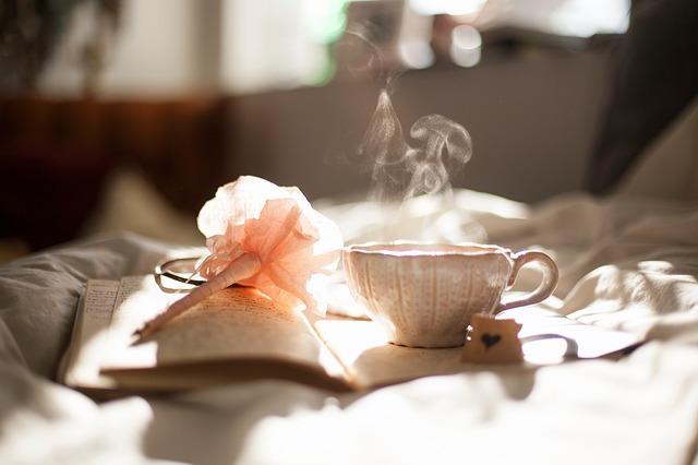 朝日の中温かい飲み物を飲みながらノートをつける画像