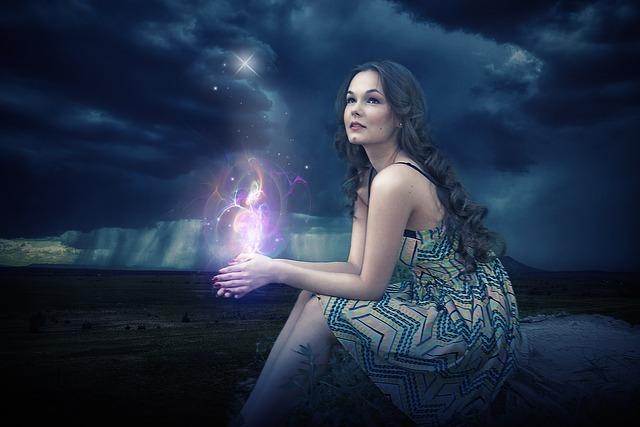 神秘的空間に座っている女性の手から光があふれている