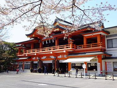 桜の木の向こうに朱色の神社がある