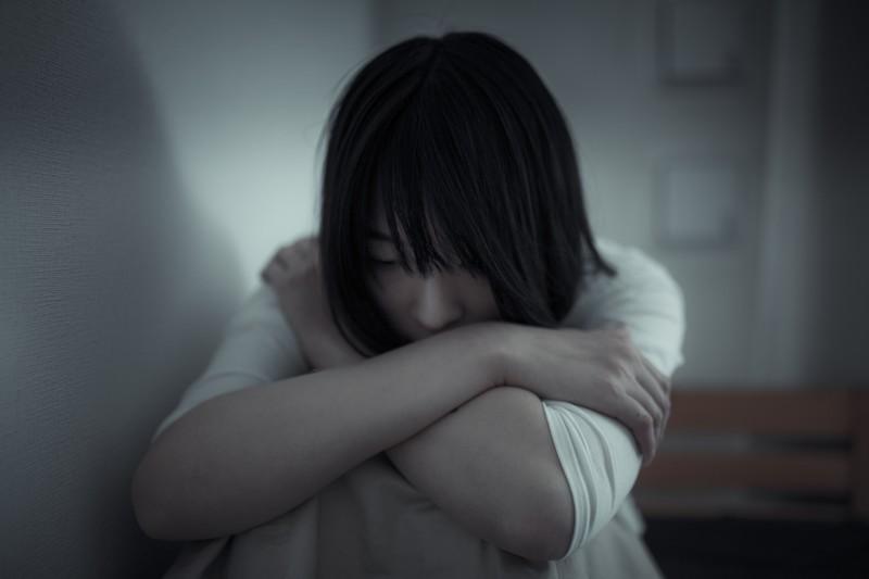 壁の横で膝を抱えてうつむく女性