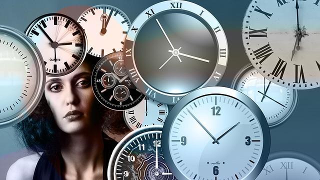 複数の時計の後ろに正面を見ている女性がいる