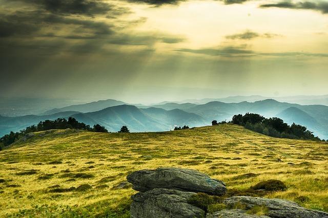 連なる山々に雲の隙間から光が差し込んでいる