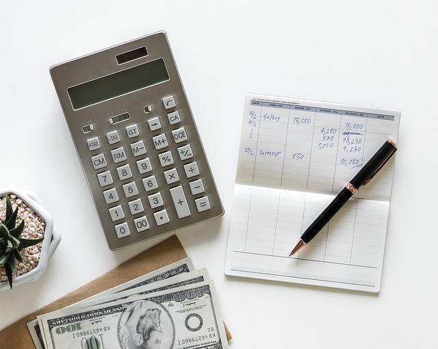 電卓と手書きの通帳とお金