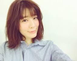 青色のシャツを着用しはにかんでいる岡本杏理