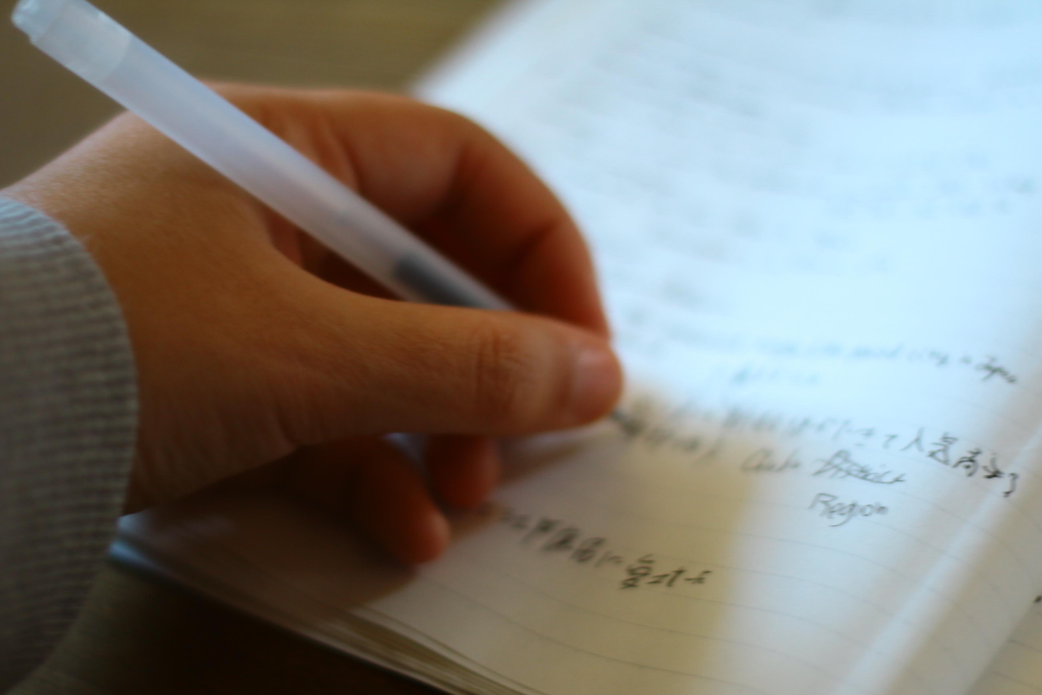 ペンを持って人が書いている写真