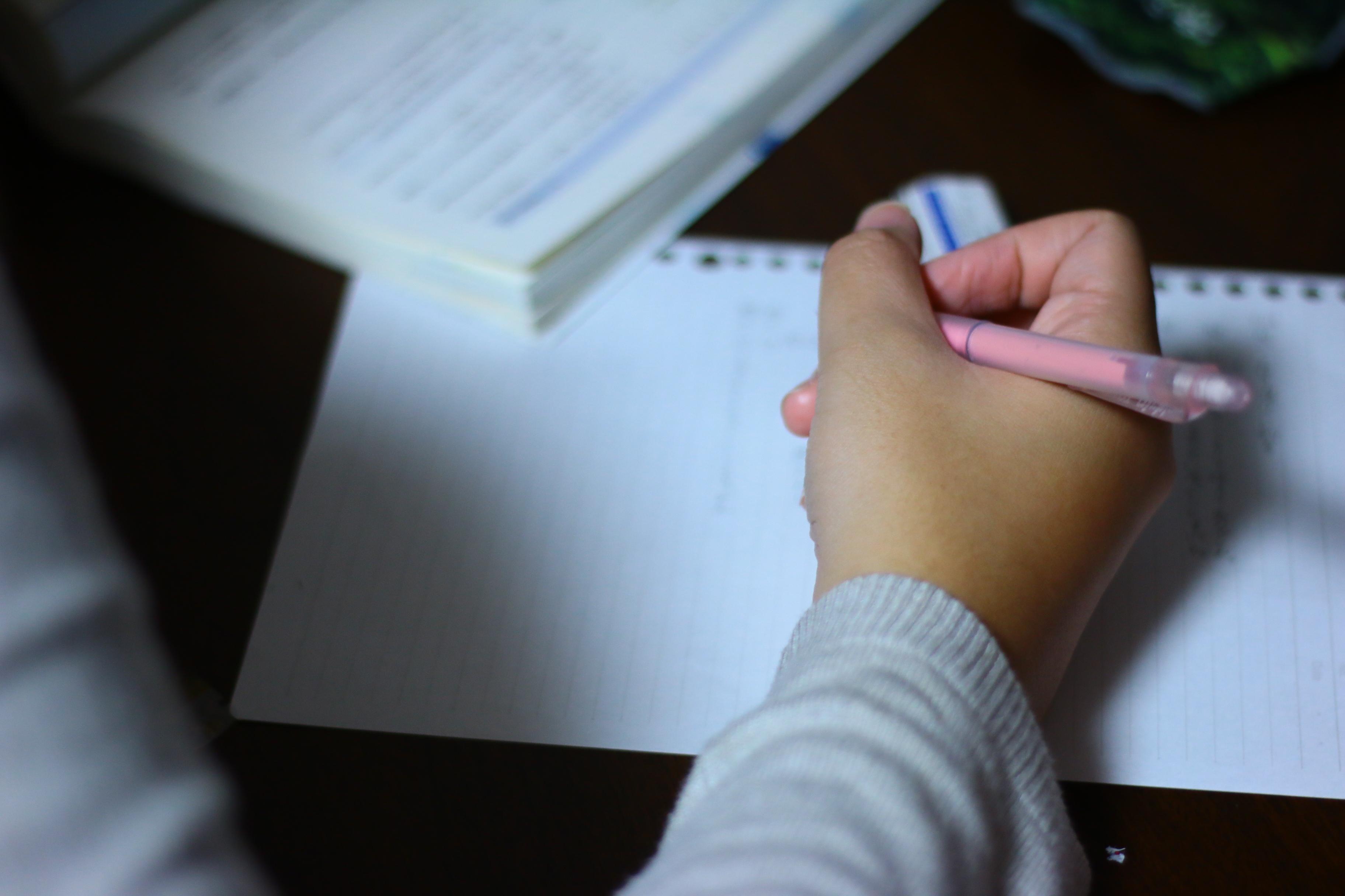 文章を書いている手の写真