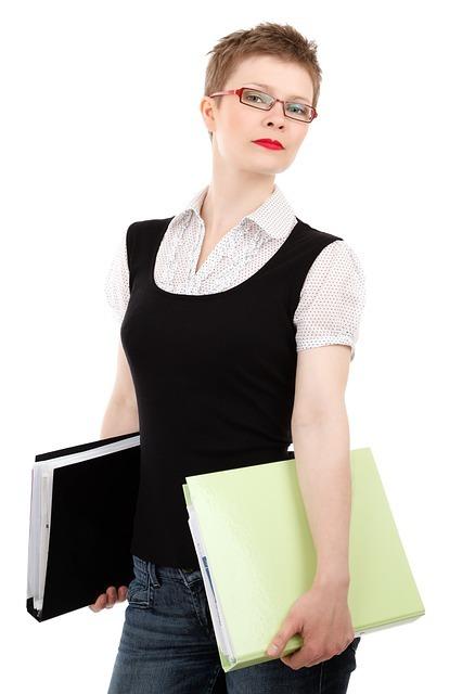 メガネをかけた女性が両手にファイルを持っている