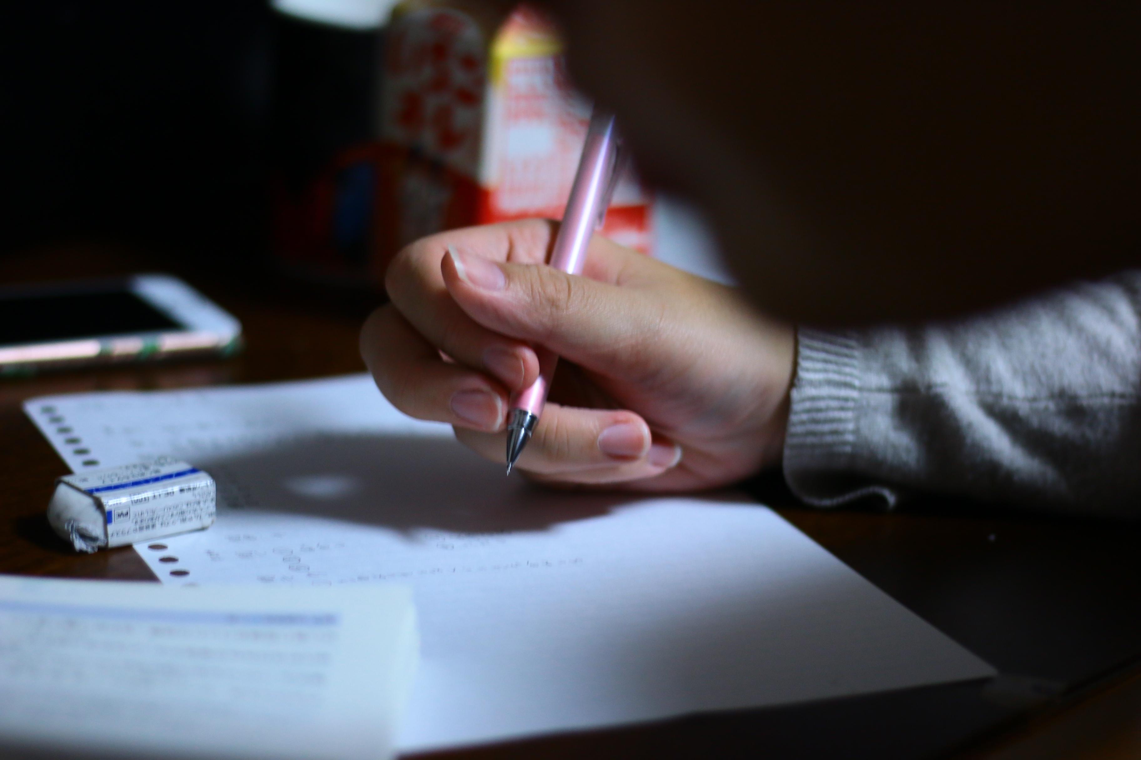 女の子がペンで何かを書いている写真
