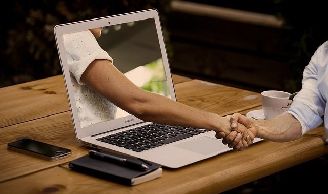 PCの中の人と手を握っている