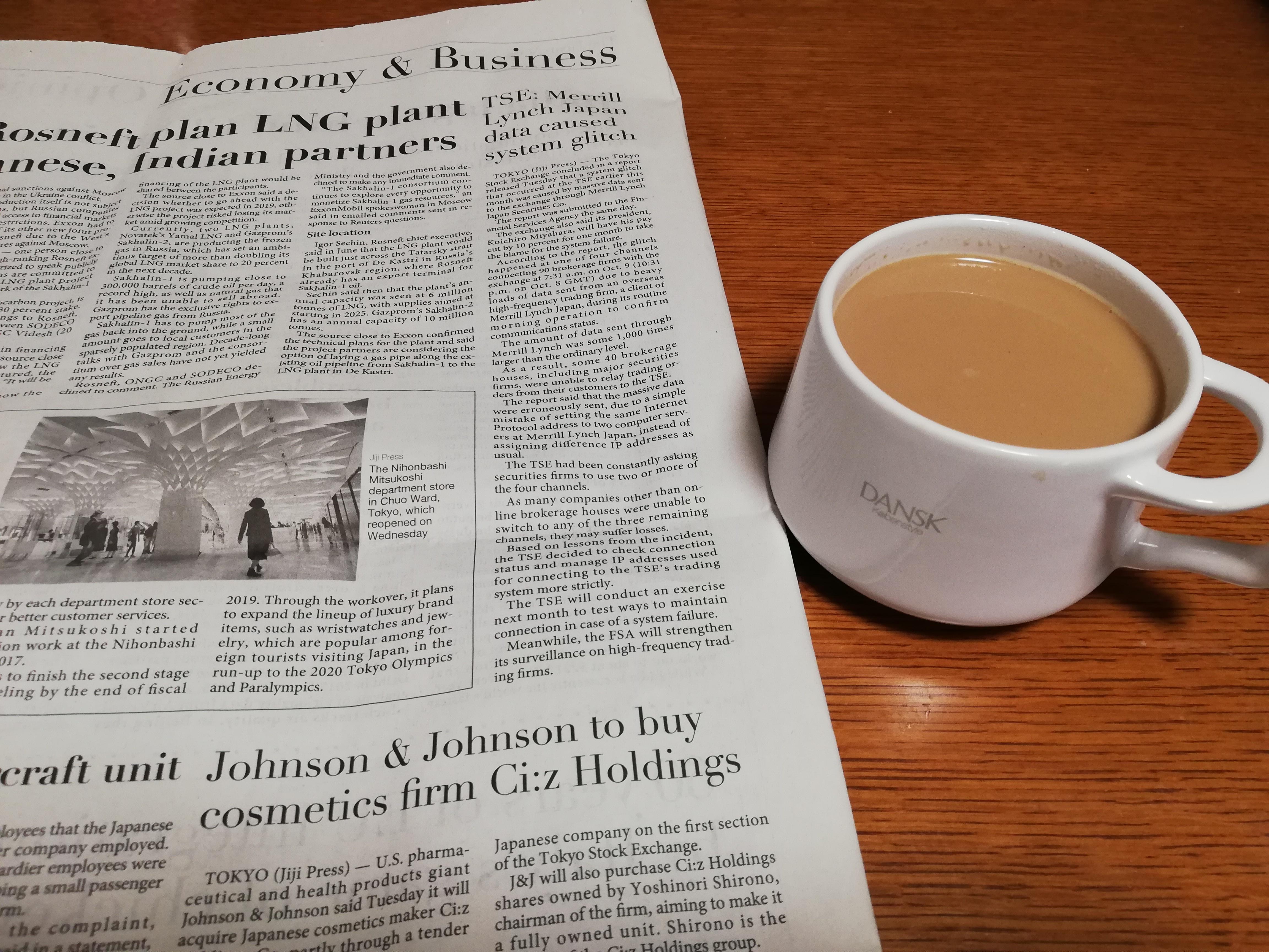 英字新聞とコーヒーの写真です。