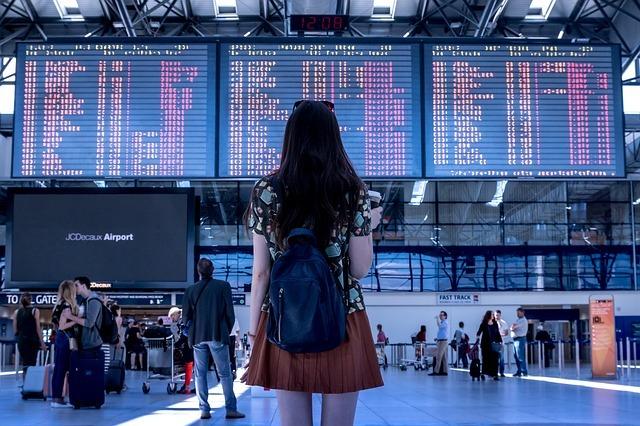 女の子が空港で時刻表掲示板をみている