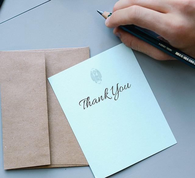 サンキューと書かれた手紙と鉛筆を持つ右手です。