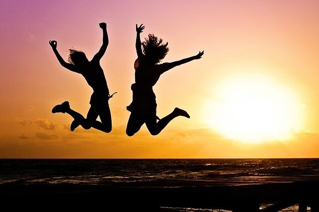 女性二人が夕日をバックにジャンプしている画像です。