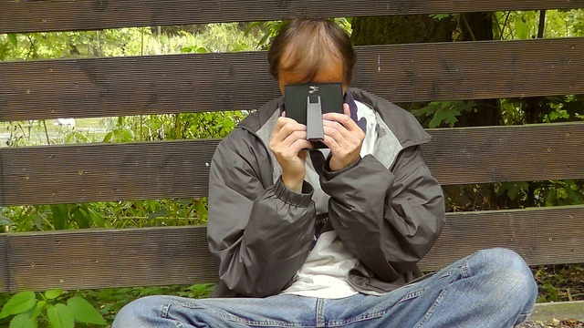 男性が座り込み顔を覆っている写真です。