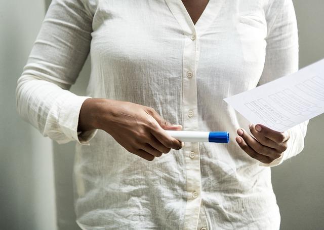 女性がペンと紙を持っている