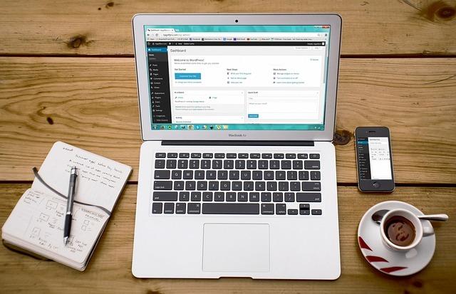 テーブルにラップトップコンピュータと携帯と手帳が置いてある写真