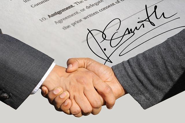 握手している男性の手とサインの写真