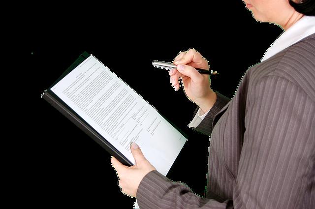 女性が書類を持ってサインしようとしている写真