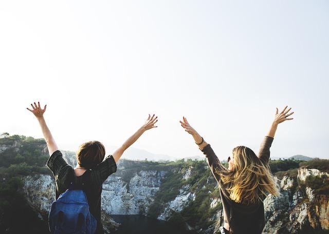女の人が二人で両手を挙げている写真です。