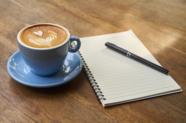 コーヒーとノートとペンが机の上にあります。