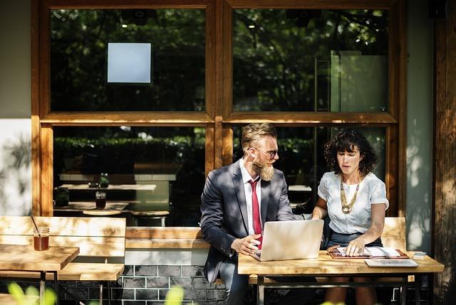 カフェのテラス席でスーツの男の人と女の人が会話をしている