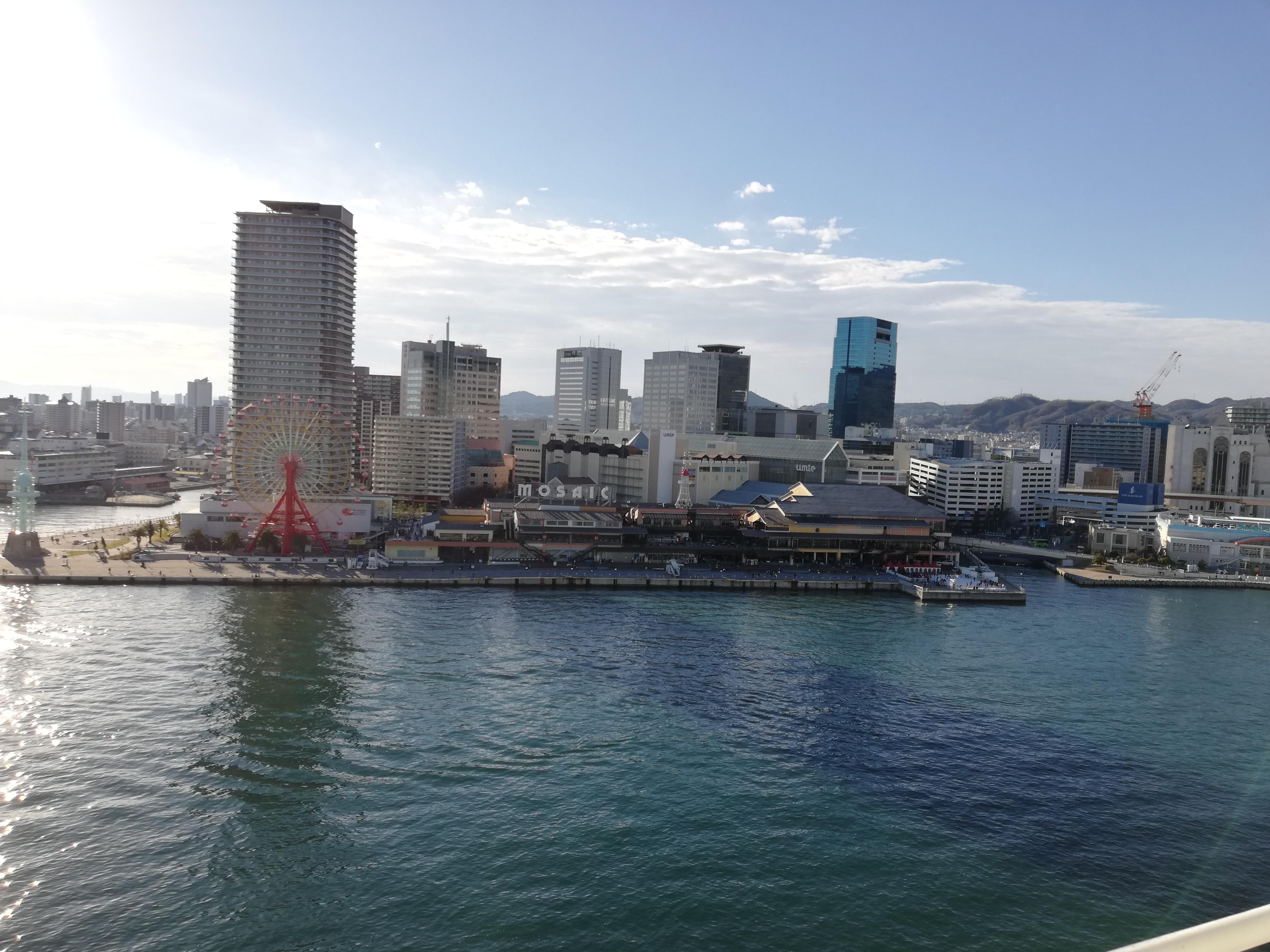 観覧車とビルと海の写真です。
