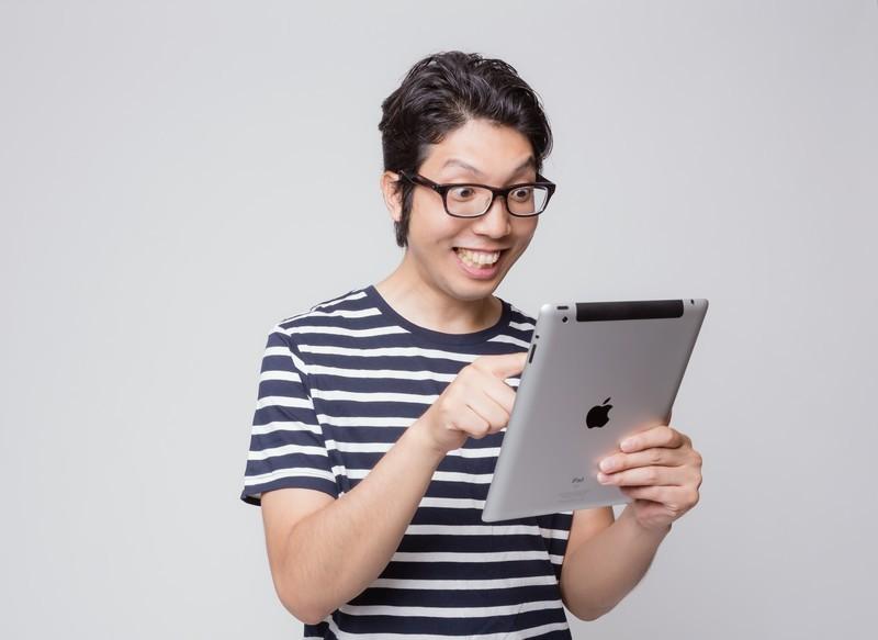 iPadを見ている男性の画像です。