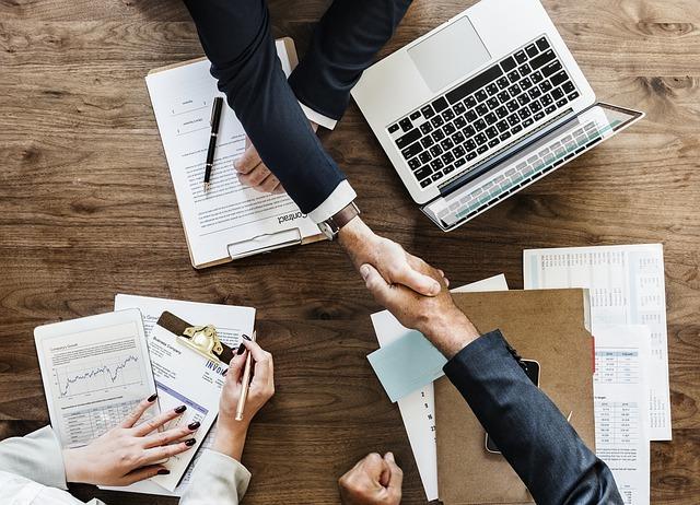 机の上にパソコンと書類。男の人たちが握手をしている。女の人もペンを持っている