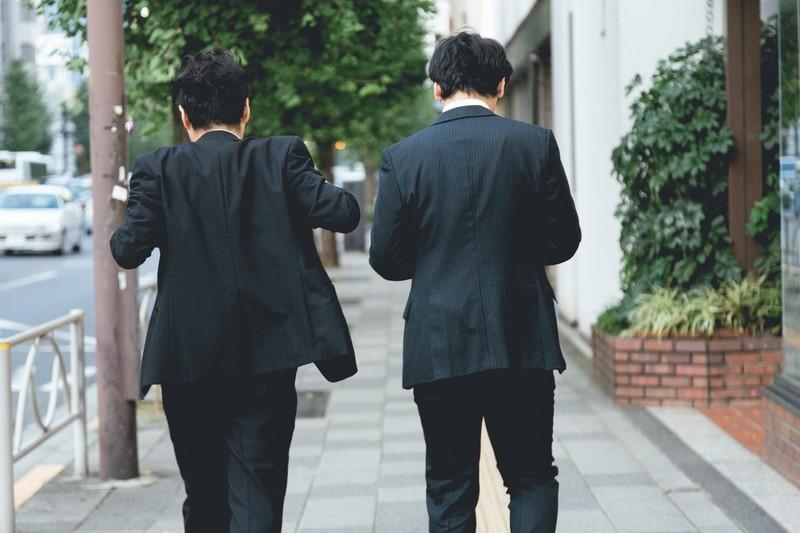 スーツの男性2人が道を歩いている