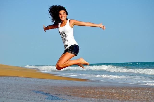 笑顔で飛び跳ねる女性です。