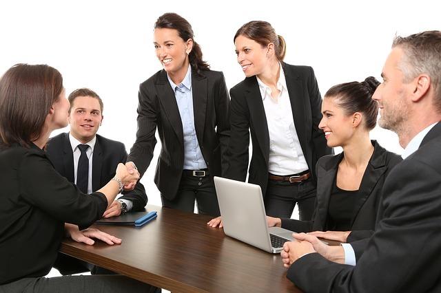 会議で女性二人がみなのまえで握手をしている