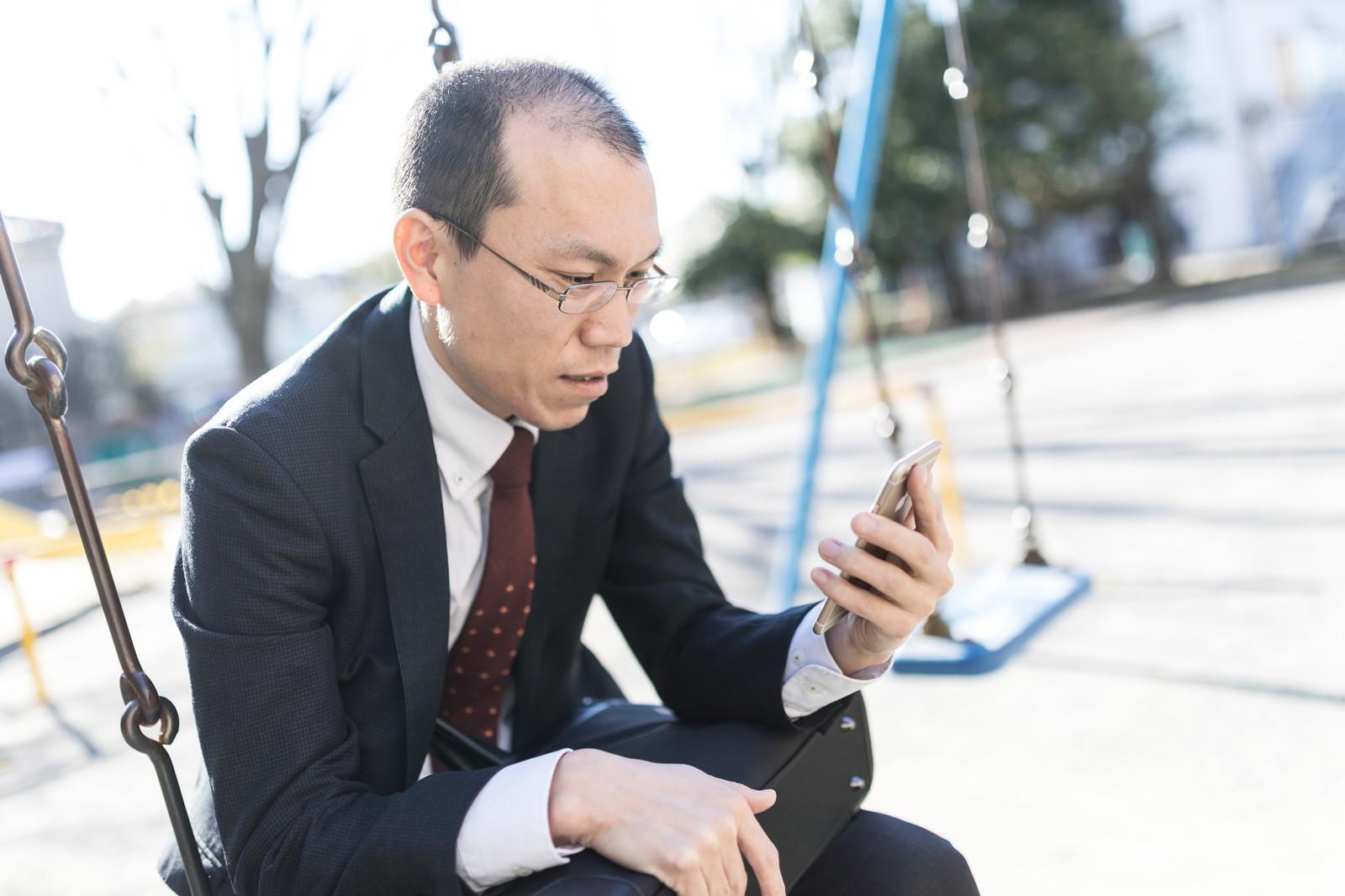 スマホをつかって公園で英語レッスンを受講している写真