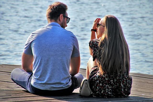 男女が海の側で会話している