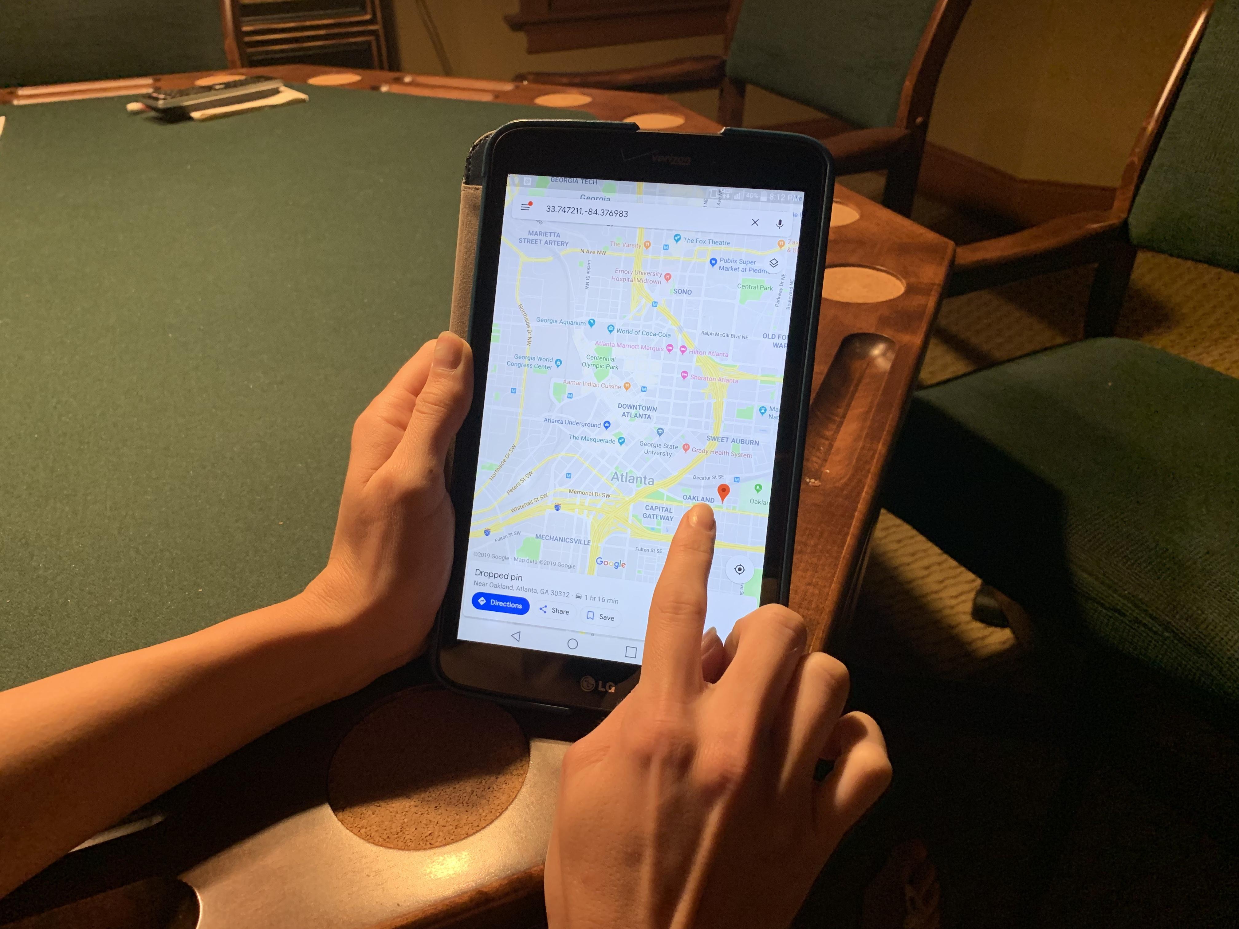 Androidのタブレット、Google Map、女性の手、カジノルームのテーブル
