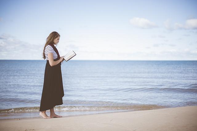 海辺で立って本を読む女性