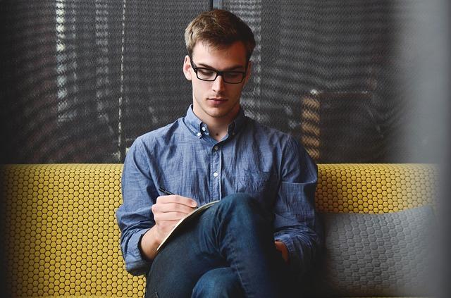 何かを書いている男性
