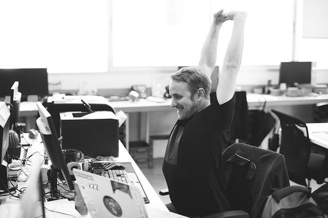 コンピュータの前で笑顔で伸びをする男性