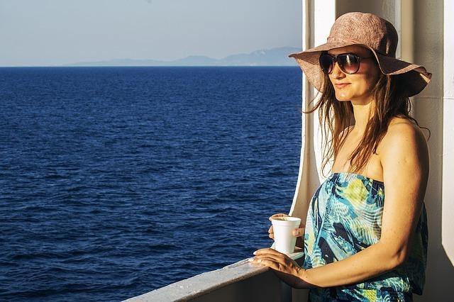 カップを片手に海を眺めるサングラスと帽子の女性の写真