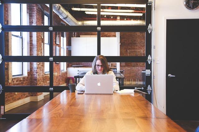 めがねの女性がオフィスでラップトップを使っている